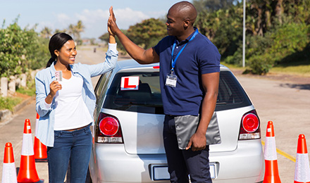 young driver giving high five to instructor