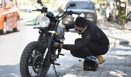 Guy working on motorcycle in the street