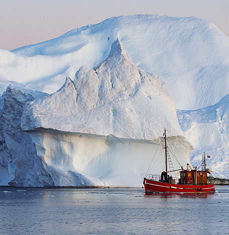 image of fishing boat next to glacier