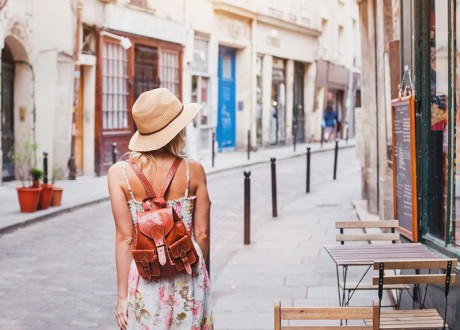 A woman wearing a small leather backpack walks down a narrow old city street with a brick road to her left and an outdoor cafe on her right.