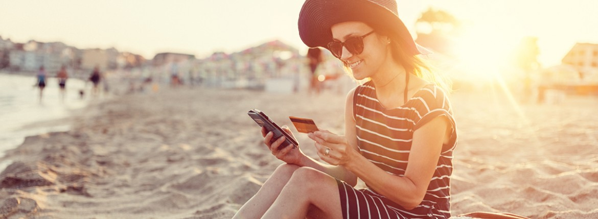 Woman holding a credit card in one hand and smartphone in the other, sitting with smile on her face, sitting on the beach sunset in background.