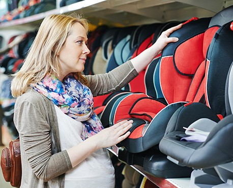 Pregnant woman inspecting a car seat while shopping